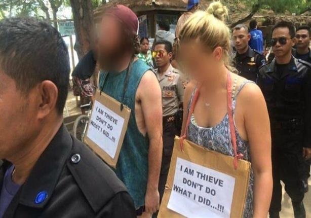 """سائحان غربيان في إندونيسيا يجبران بعد السرقة على حمل لافتة تقول """"أنا سارق"""""""